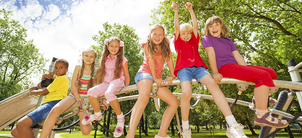 Kids sit on round bar of playground construction and one boy holds up hands in the air up